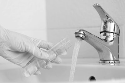 Tap water analysis quality control concept. Hand with a flask an